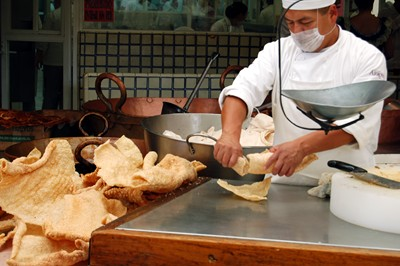 A cook weighs out some chicharrones, or fried pork skins.