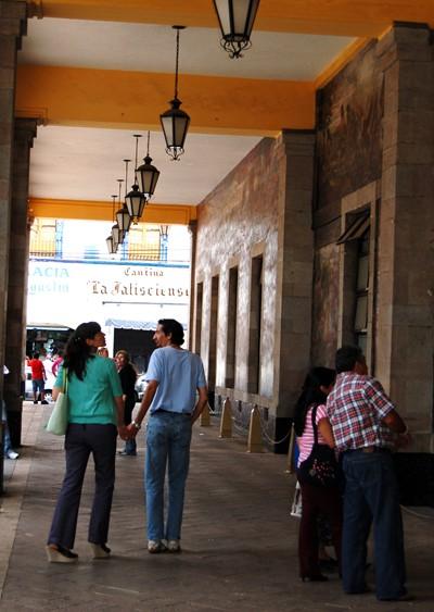 A couple admires a mural in Tlalpan's zocalo.