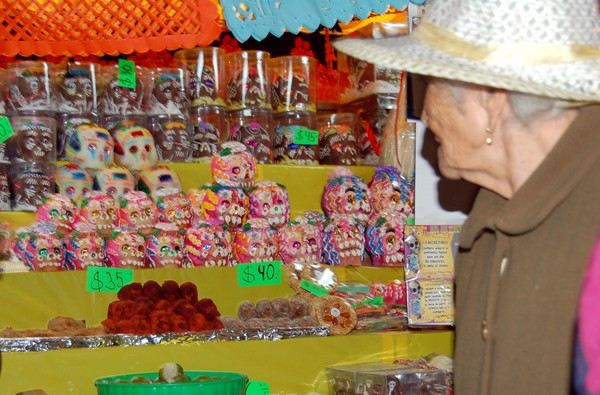 An older woman checks out some skulls for sale.
