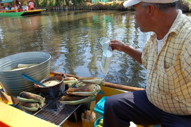 A man sells roasted corn in the floating gardens of Xochimilco.
