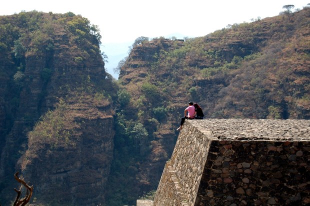 A couple enjoys the view from one of the ancient pyramids perched above town.