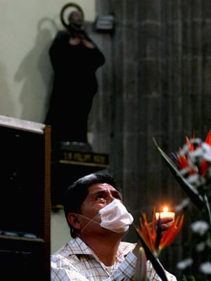 "A man in a Mexico City church prays with a ""tapaboca"" -- face mask. <sub>Photo by Flickr user Alma Rodriguez Ayala.</sub>"