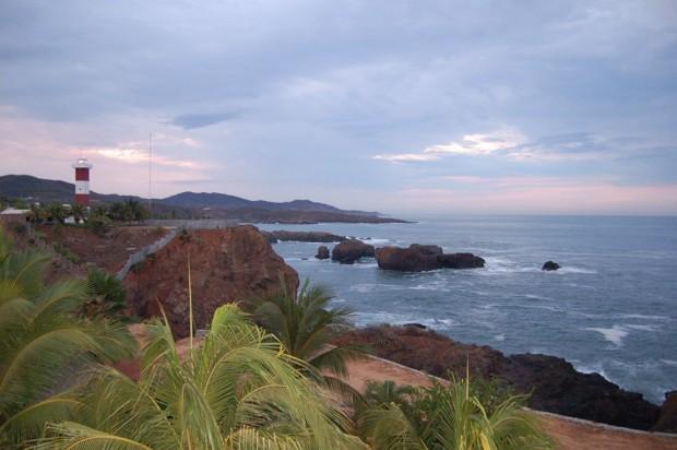 The sun rises behind the lighthouse, Caleta de Campos.