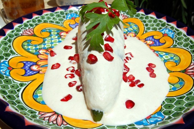 A poblano pepper stuffed with spicy pork and fruit, covered in a walnut cream sauce, and doused with pomegranate seeds. It's a rough life.